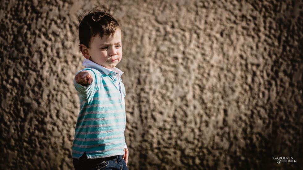 petit garçon pointant du doigt devant un mur crépi