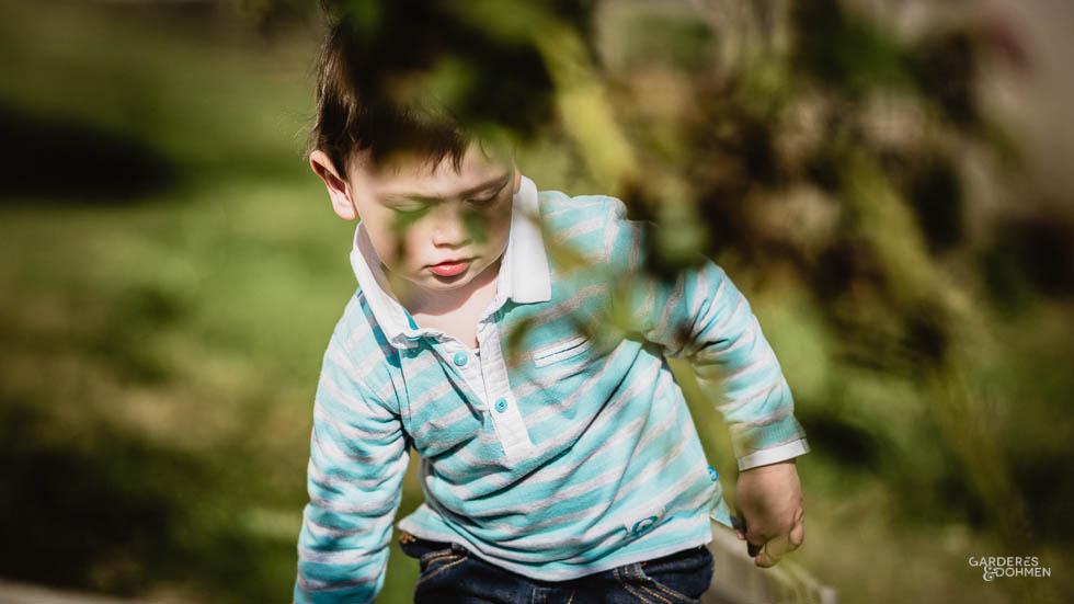 petit garçon derrière des feuillages