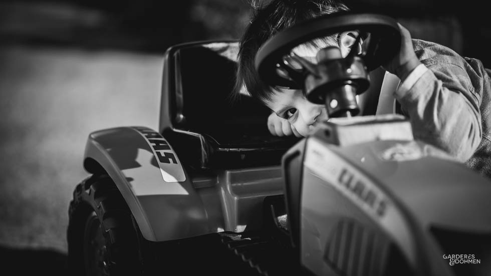 petit garçon se cachant derrière son tracteur