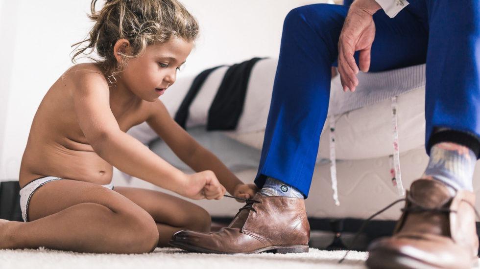 Petite fille faisant les lacets du marié